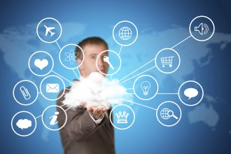 Business man hold cloud with computer icons in hand. Technology concept. World map as backdrop